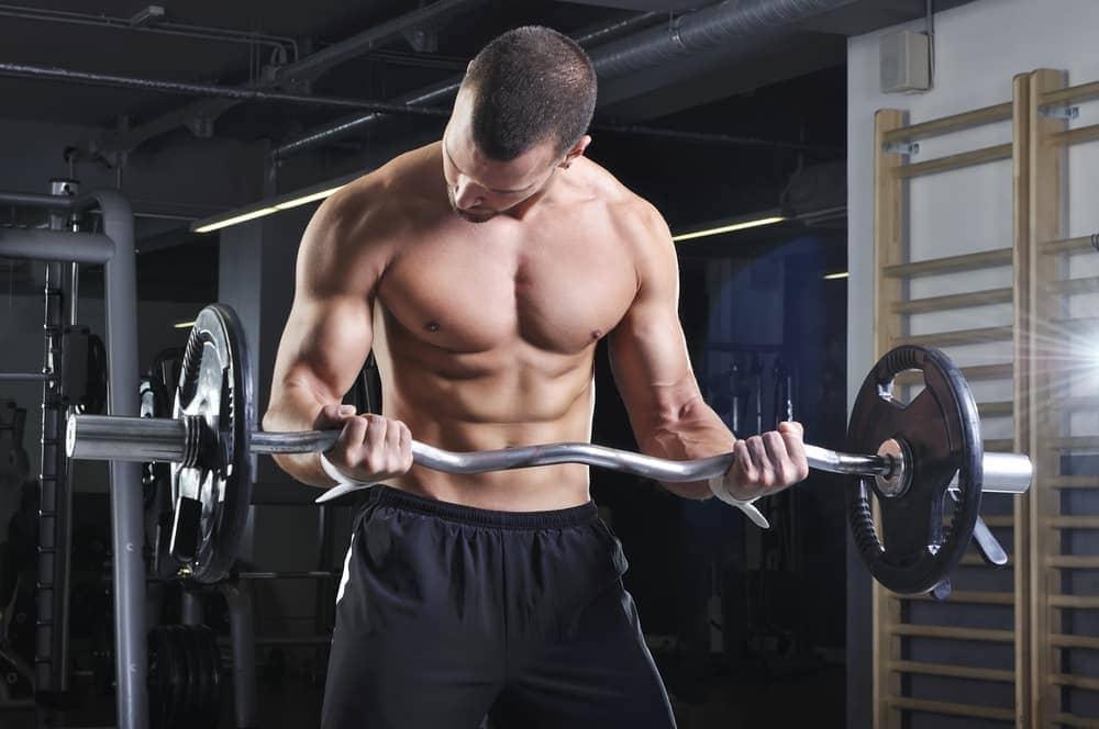 hombre haciendo biceps curl con barra Z en el gimnasio