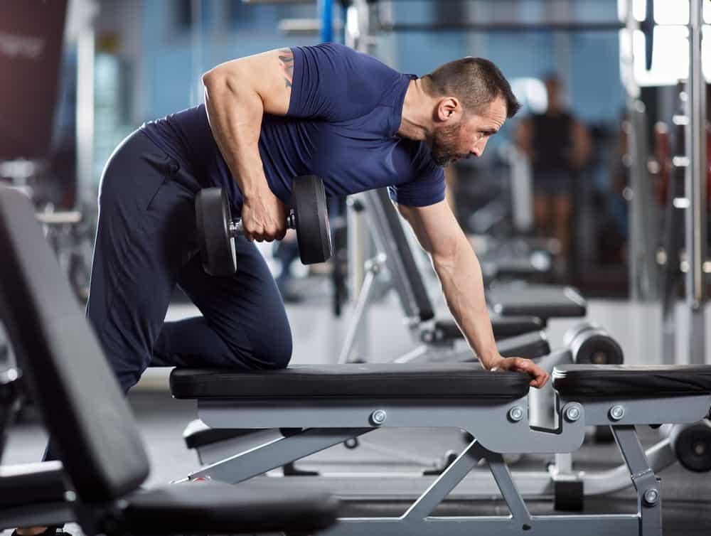 hombre haciendo ejercicio de espalda en un banco de pesas