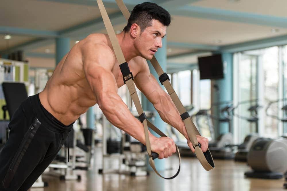 Hombre entrenando con un kit de entrenamiento en suspensión