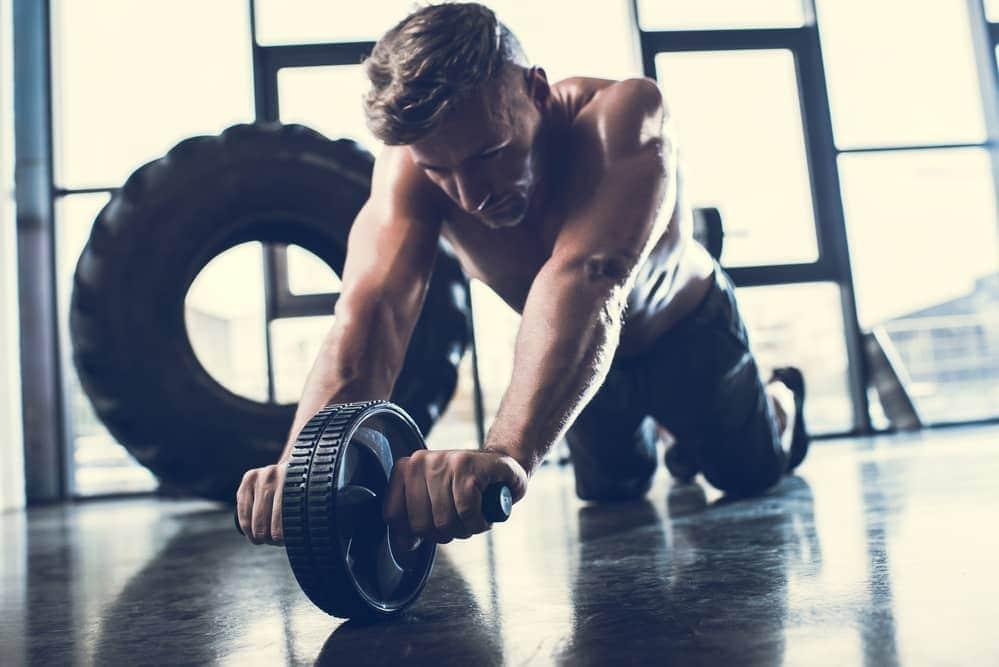 Hombre deportista haciendo ejercicio con una rueda de abdominales