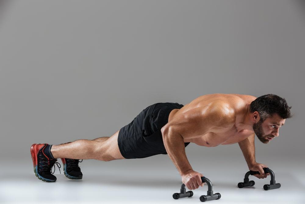 Hombre haciendo flexiones con un soporte