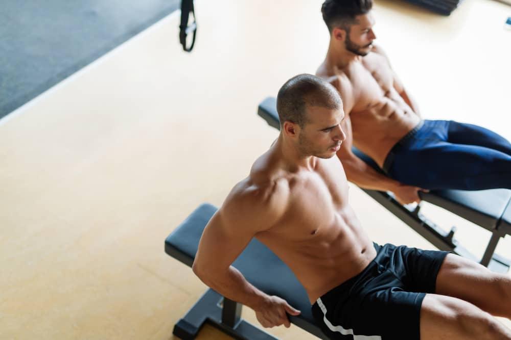 Hombres entrenando en bancos de abdominales baratos