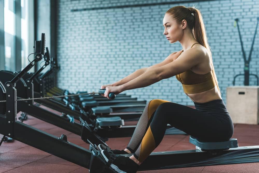 Mujer entrenando con la mejor máquina de remo para casa