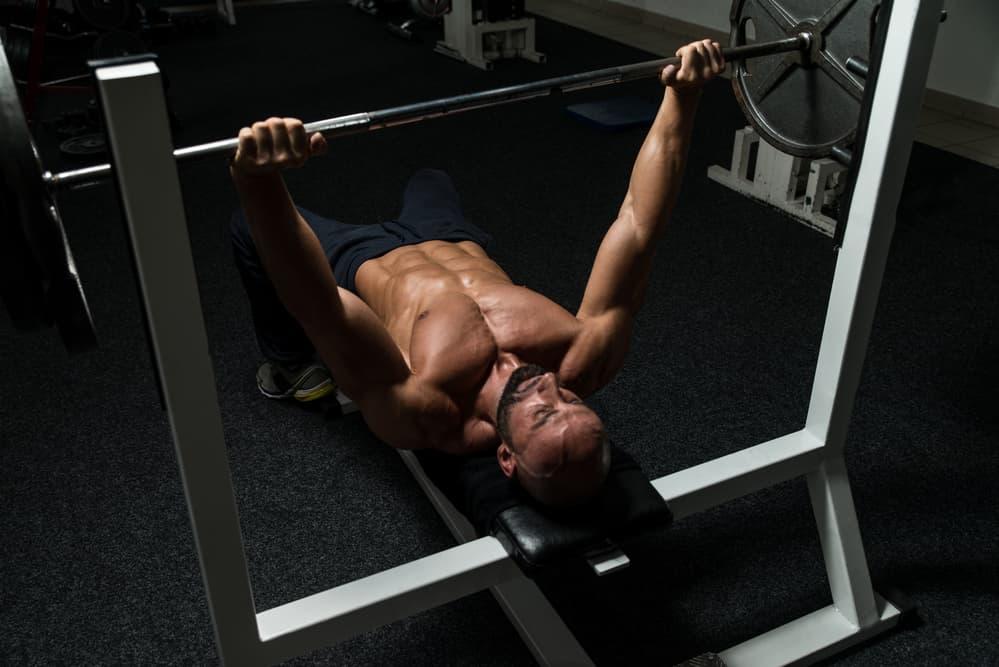 Hombre entrenando con un rack gimnasio