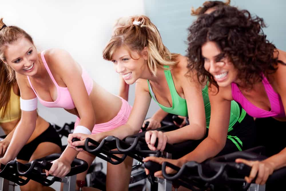 Mujeres entrenando en bicicletas estáticas con respaldo