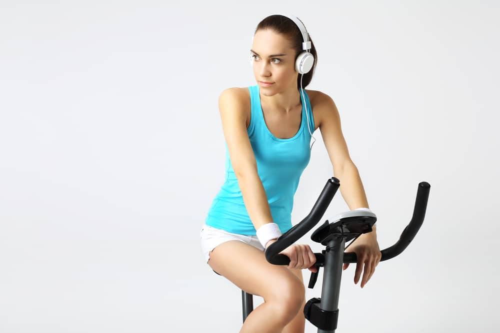 Mujer entrenando en bicicletas estáticas baratas