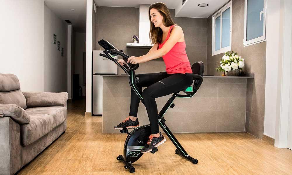 Mujer entrenando en una bicicleta estática cecotec